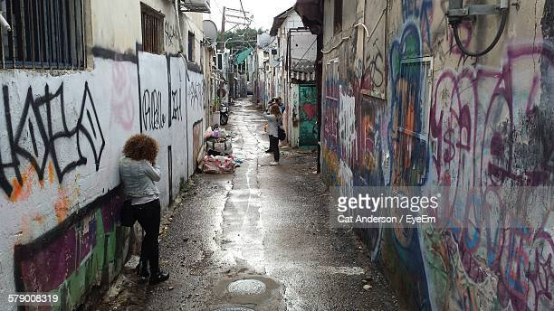 People Photographing In Wet Alley Amidst Graffiti Walls
