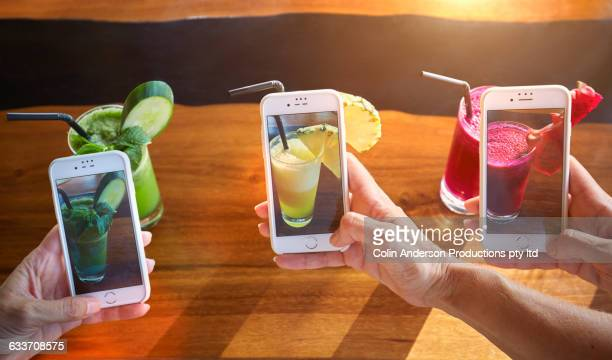 People photographing juice with cell phone