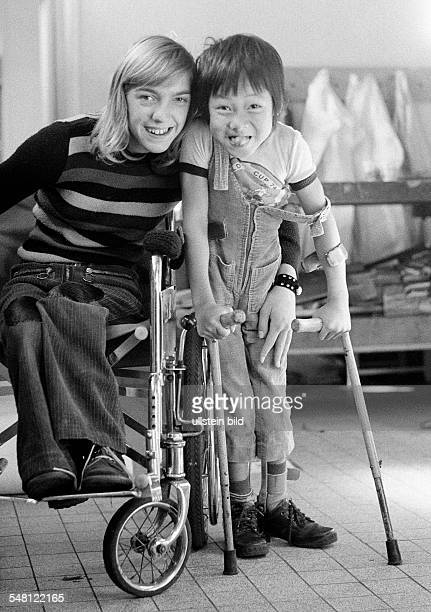 people physical handicap girl in a wheelchair and boy from Vietnam with crutches posing boy sticks out the tongue aged 11 to 14 years aged 6 to 10...