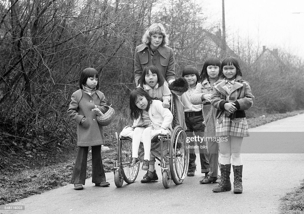 people, physical handicap, refugees, childrens nurse and six girls from Vietnam, one girl sits in a wheel-chair, aged 16 to 20 years, aged 4 to 12 years, Friedensdorf Oberhausen, D-Oberhausen, Ruhr area, North Rhine-Westphalia - 31.12.1973 : News Photo