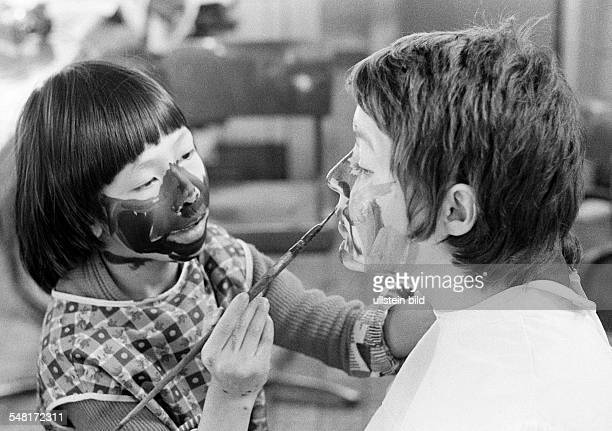 People, physical handicap, school lessons, fostress and a boy from Vietnam paint their faces with a paintbrush each other, aged 20 to 25 years, aged...