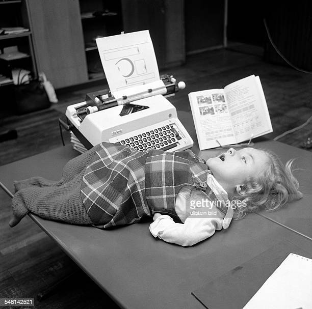 people physical handicap school lessons schoolgirl lies on a table and types on a typrwriter aged 4 to 8 years Carola Special School Alsbachtal...