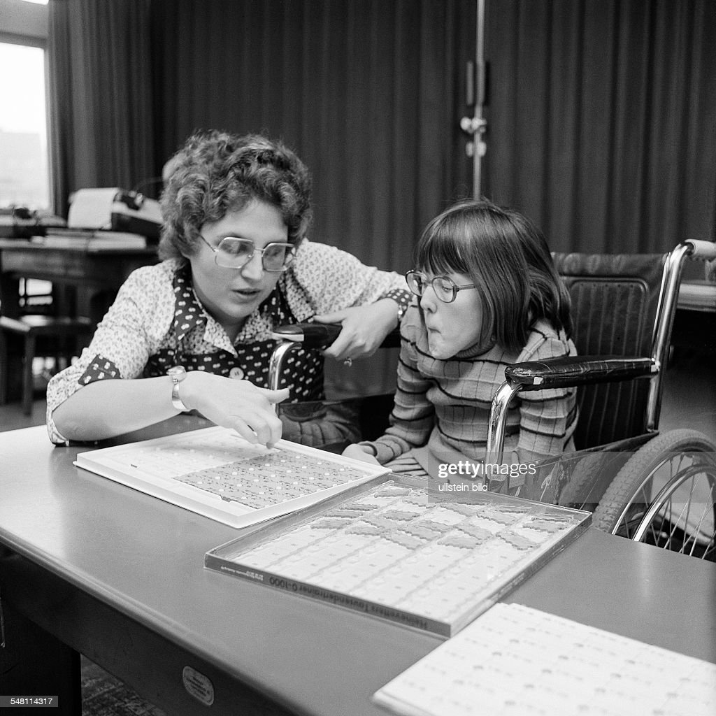 people, physical handicap, school lessons, teacher assists a girl sitting in a wheel-chair in the exercises, aged 30 to 40 years, aged 8 to 12 years, Special School Alsbachtal, D-Oberhausen, D-Oberhausen-Sterkrade, Ruhr area, North Rhine-Westphalia - : News Photo