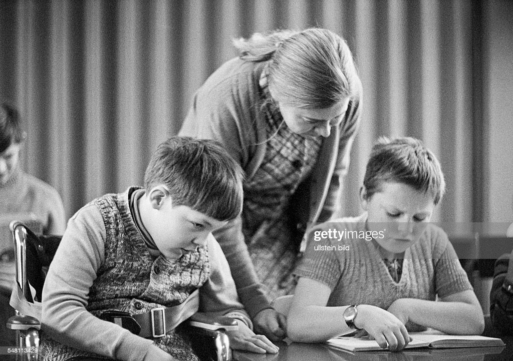 people, physical handicap, school lessons, teacher assists two boys in the exercises, reading, aged 30 to 40 years, aged 10 to 14 years, Maria, Special School Alsbachtal, D-Oberhausen, D-Oberhausen-Sterkrade, Ruhr area, North Rhine-Westphalia - 30.11 : Nieuwsfoto's