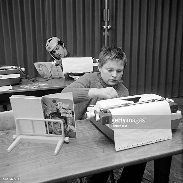 people physical handicap school lessons two school boys type on a typewriter one of them strikes the keys with a beater fixed at his head aged 14 to...