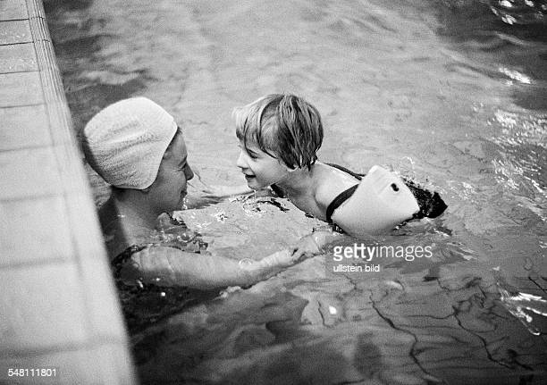 people physical handicap swimming lessons teacher assists young girl in swimming exercises arm floats water wings aged 30 to 40 years aged 6 to 8...