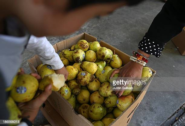 People pick through a box of pears as they wait in line to receive free food at the Richmond Emergency Food Bank on November 1 2013 in Richmond...