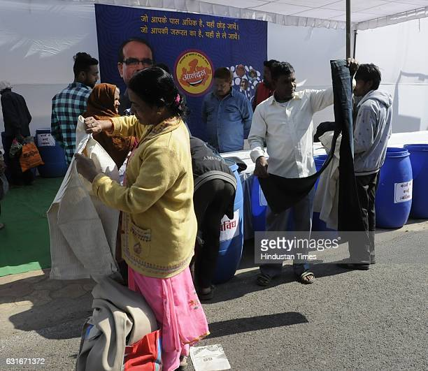 People pick up clothes from a collection box installed during an inauguration of weeklong programme of Happiness Department 'Anandam' on the occasion...
