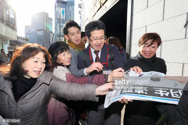 People pick up the special edition of newspaper reporting that Yuzuru Hanyu of Japan won the gold medal in the PyeongChang Winter Olympic Games...