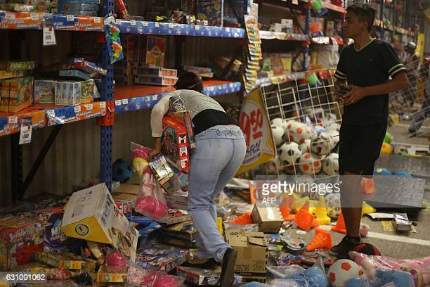 People pick up toys as they loot a store during a protest in the port of Veracruz Mexico on January 4 related to a 20 percent gasoline price increase...