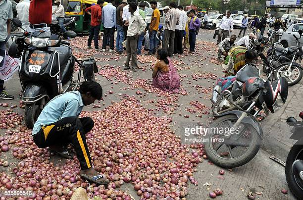 People picking up onions that were thrown by farmers from Bijalpur and Rau as part of their protest in front of Collectorate on May 30 2016 in Indore...
