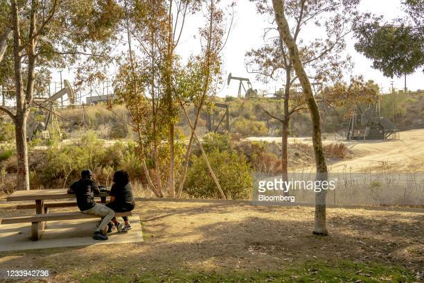 People picnic at Kenneth Hahn State Recreation Area in front of An oil pump jack operating at the Inglewood Oil Field in Culver City, California,...