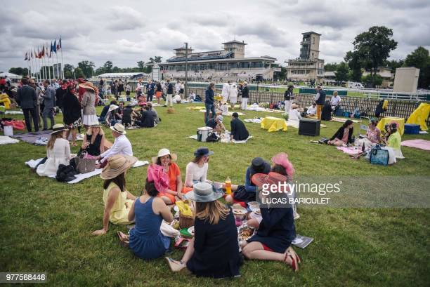 People picnic during the 169th Prix de Diane horse racing on June 17, 2018 in Chantilly, northern Paris.