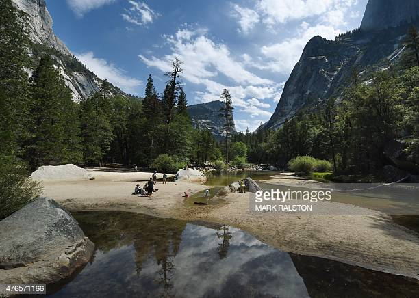 People picnic on the exposed sandy bottom of Mirror Lake that is normally underwater and used by visitors to photograph reflections of the Half Dome...