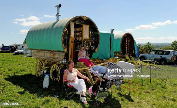 People pictured by a Romany caravan at the Appleby Horse Fair the annual gathering of gypsies and travellers in Appleby Cumbria