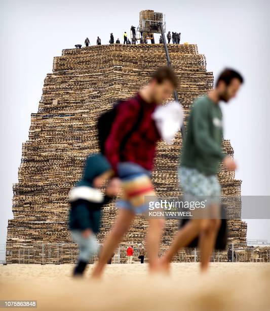 People pile up wooden pallets prior to the traditional bonfire of New Year eve on the beach of Scheveningen on december 30 2018 Two dutch villages...