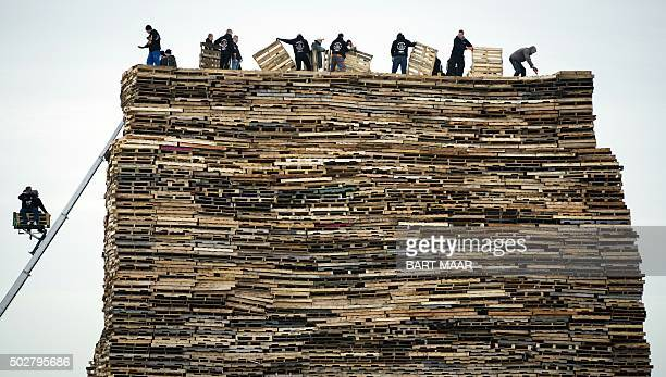 People pile up wooden pallets prior to the traditional bonfire of New Year eve on december 29 2015 in Scheveningen / AFP / ANP / Bart Maar /...