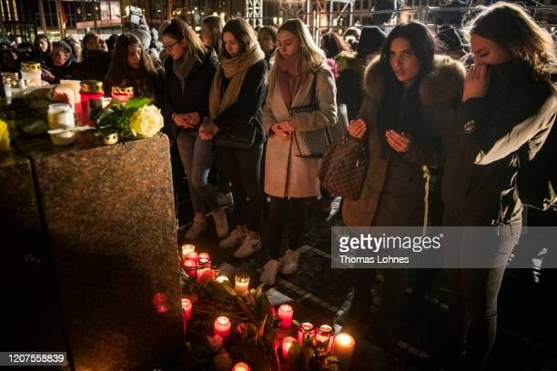 People place candles and flowers at the 'Brueder Grimm' monument after a vigil for the victims near the Midnight shisha bar one of the sites of last...