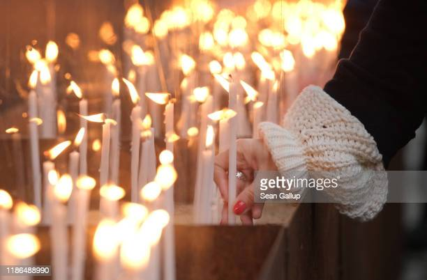 People place candles at a memorial to the Berlin Wall at Bernauer Strasse following a ceremony to celebrate the 30th anniversary of the fall of the...