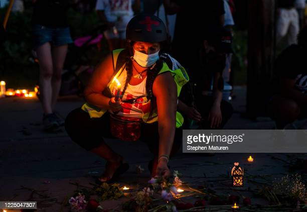 People place candles during a vigil in honor of Philando Castile, at the site where he was killed, on July 6, 2020 in Falcon Heights, Minnesota....