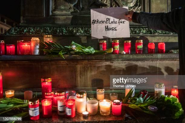 People place candles flowers and signs against racism at the 'Brueder Grimm' monument after a vigil for the victims near the Midnight shisha bar one...
