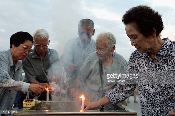 People place candles to pray for abomb victims at the Peace Memorial Park on August 6 2004 in Hiroshima Japan Hiroshima marks the 59th anniversary of...