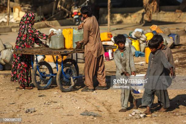People place containers filled with water on a cart in Karachi Pakistan on Saturday Dec 22 2018 Women and children walk miles each day in search...