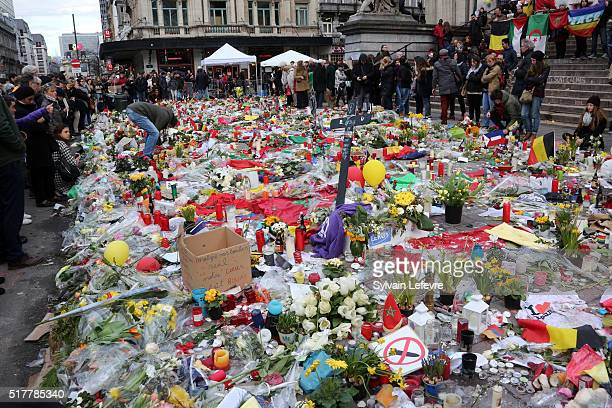 People place flowers and candles in the Place de la Bourse to pay tribute to the 31 victims of the attacks in Brussels last week on March 27 2016 in...