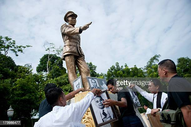 People place flowers and photographs around a statue of General Aung San to mark Martyrs' Day in Yangon on July 19 2013 General Aung San and eight...