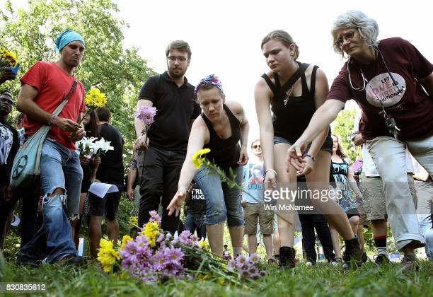 People place flowers at a makeshift memorial during a vigil for those who were injured and died when a car plowed into a crowd of antifacist...