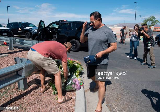 People place flowers at a makeshift memorial outside the Cielo Vista Mall WalMart where a shooting left 20 people dead in El Paso Texas on August 4...