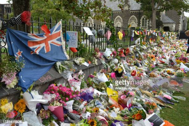 People place flowers at a memorial as a tribute to victims of the Fridays terrorist attacks on two mosques that left at least 50 people killed in...