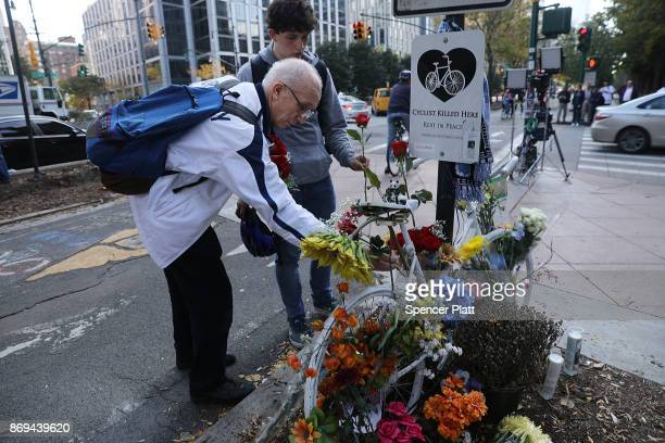 People place flowers at a memorial at the scene of Tuesday's terrorist attack along a bike path in lower Manhattan on November 2 2017 in New York...