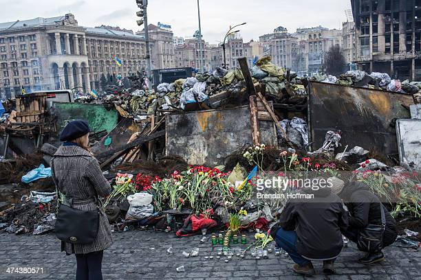People place flowers at a memorial to antigovernment protesters killed in chashes with police on Independence Square on February 23 2014 in Kiev...