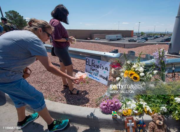 People place flowers beside a makeshift memorial outside the Cielo Vista Mall WalMart where a shooting left 20 people dead in El Paso Texas on August...