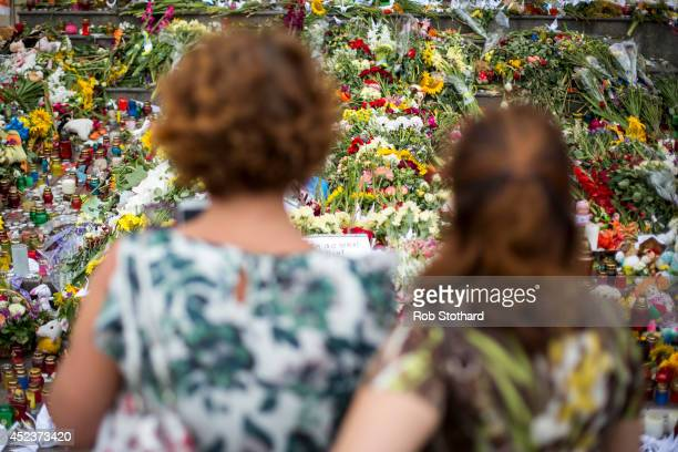 People place flowers candles and other tributes in front of the Netherlands Embassy in memory of the victims of Malaysia Airlines flight MH17 on July...