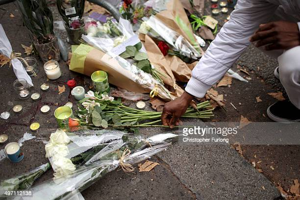 People place flowers on the pavement near the scene of yesterday's Bataclan Theatre terrorist attack on November 14 2015 in Paris France At least 120...