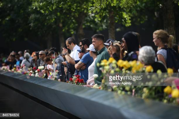 People place flowers over the monument for the 9/11 attacks victims on the 16th anniversary of the 9/11 in Ground Zero Manhattan New York United...