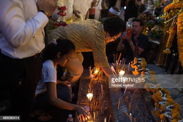 People place incense, candles and pour water at the base of the Erawan Shrine to commemorate the victims of the Bangkok bomb attack on August 24,...