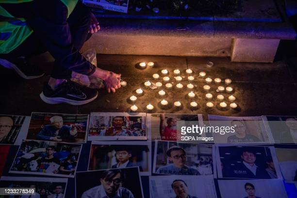 People place lit candles at a vigil outside the Chinese Embassy in London. People gather for a vigil outside the Chinese Embassy on June 4th to mark...