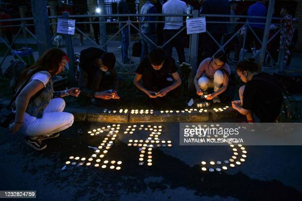 People place lit candles on the ground to form the number 175 at a makeshift memorial for victims of the shooting at School No. 175 in Kazan on May...