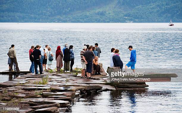 People place on July 26 2011 flowers and candles on the coast of lake Tyrifjorden infront of the Utoeya island in honor of the victims of the July 22...