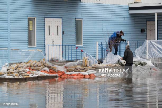 People place sand bags and plastic wrap around a church to prepare for spring flooding in Gatineau Quebec on April 20 2019