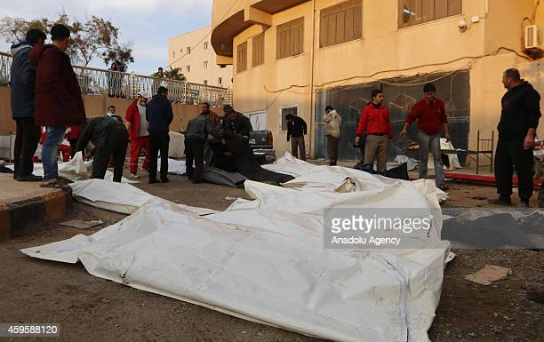 People place the bodies into body bags after the air strikes by Syrian army warplanes on the ISILheld northern city of Raqqa Syria on November 25...