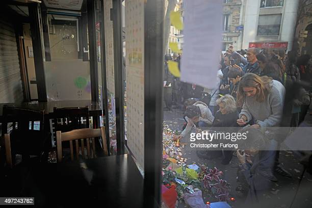 People place tributes and flowers outside La Belle Equipe restaurant on Rue de Charonne following Fridays terrorist attack and France observes three...