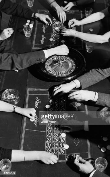 People placing their bets on a roulette table Original Publication Picture Post 8780 Amateurs Get Roulette Crazy pub 1957