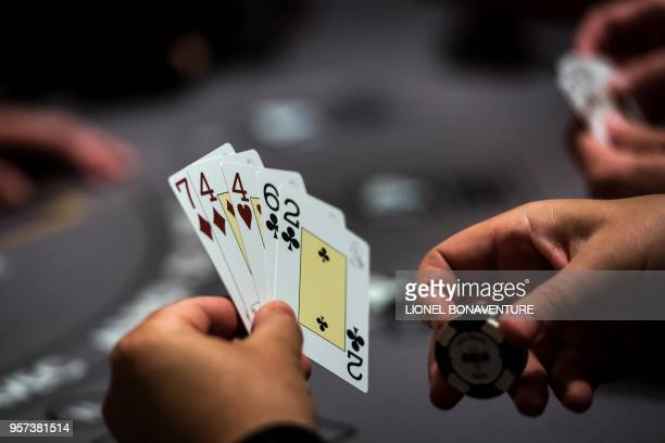 People play a card game at the Paris Elysees Club the first gaming club to open its doors in the French capital in Paris on May 9 2018 Casinos were...