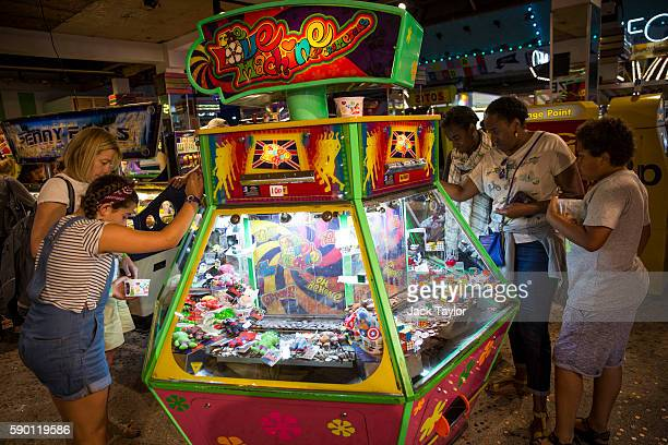 People play a slot machine in the Dreamland amusement arcade on August 16 2016 in Margate England British holidaymakers and overseas visitors flock...