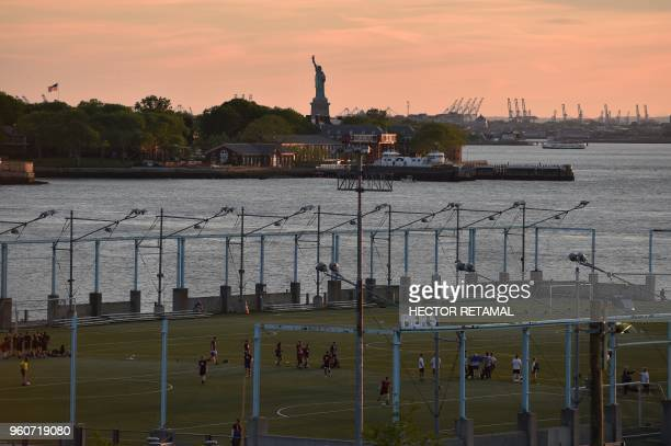 People play a soccer match during sunset at Brooklyn Bridge Park in New York City on May 20 against the background of the Statue of Liberty