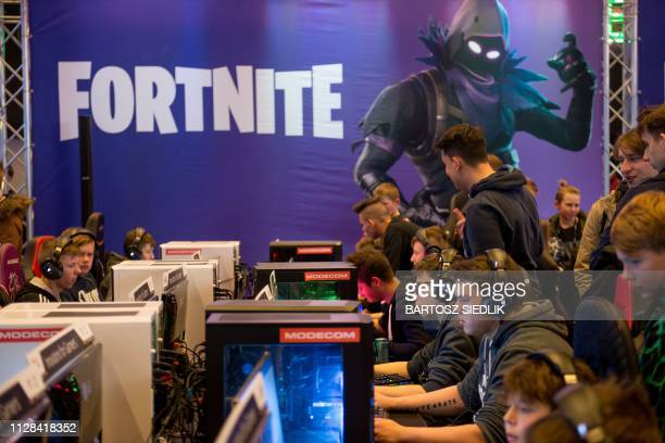 People play at computers with a Fortnite poster in the background during the Intel Extreme Masters Katowice 2019 event in Katowice on March 2 2019
